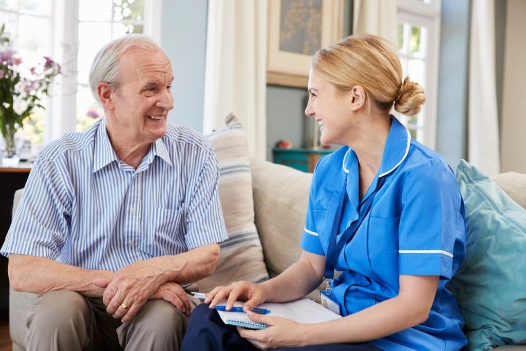 female-community-nurse-visits-senior-man-at-home-picture-id874794192