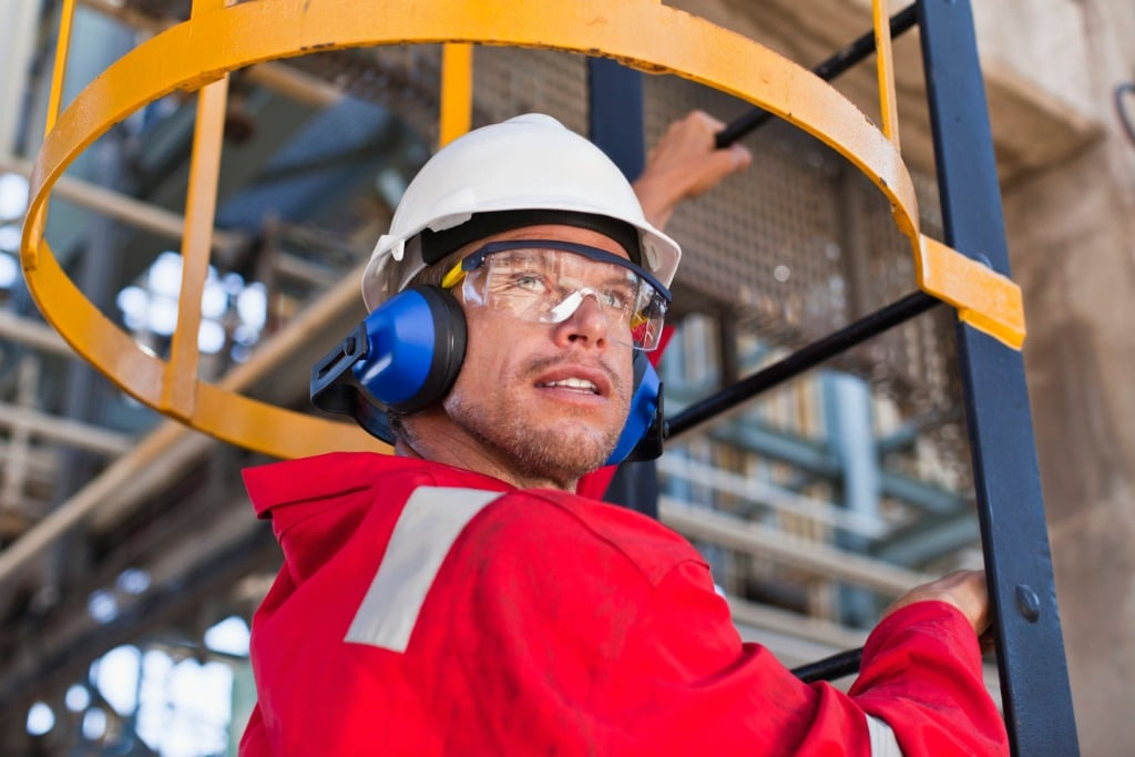 worker-climbing-ladder-at-oil-refinery-picture-id149319933