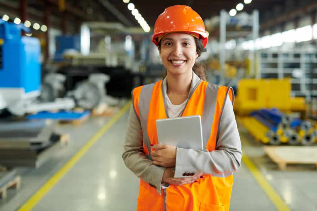 Young woman in factory with tablet