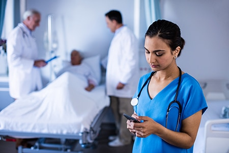 Female doctor or nurse using smartphone